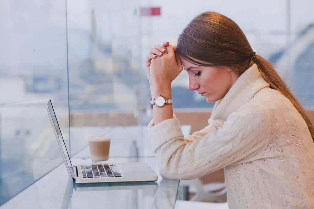 Tjej med betalningsanmärkning letar lån på sin dator