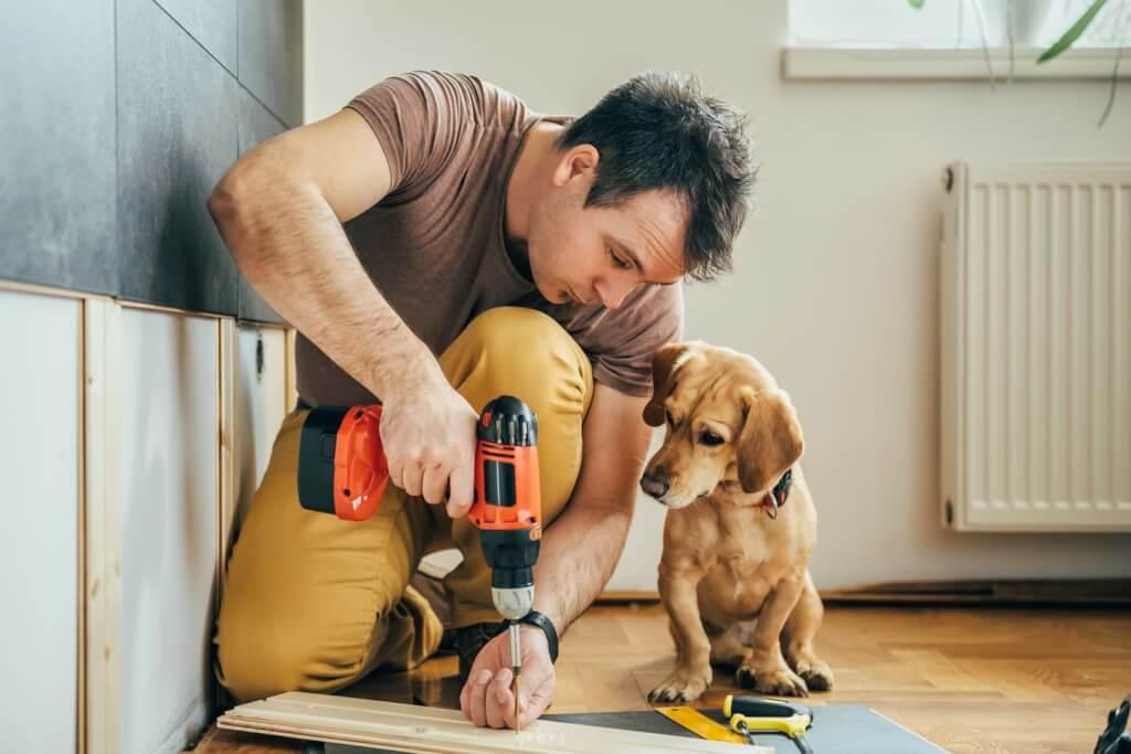 Man och hund som renoverar