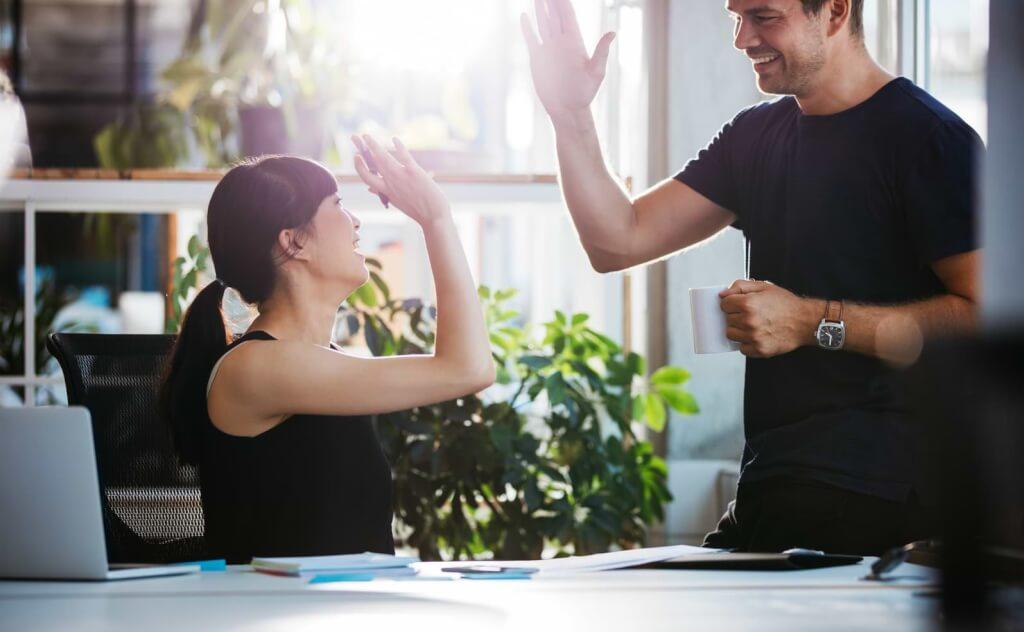 Kvinna och man gör high-five på kontor