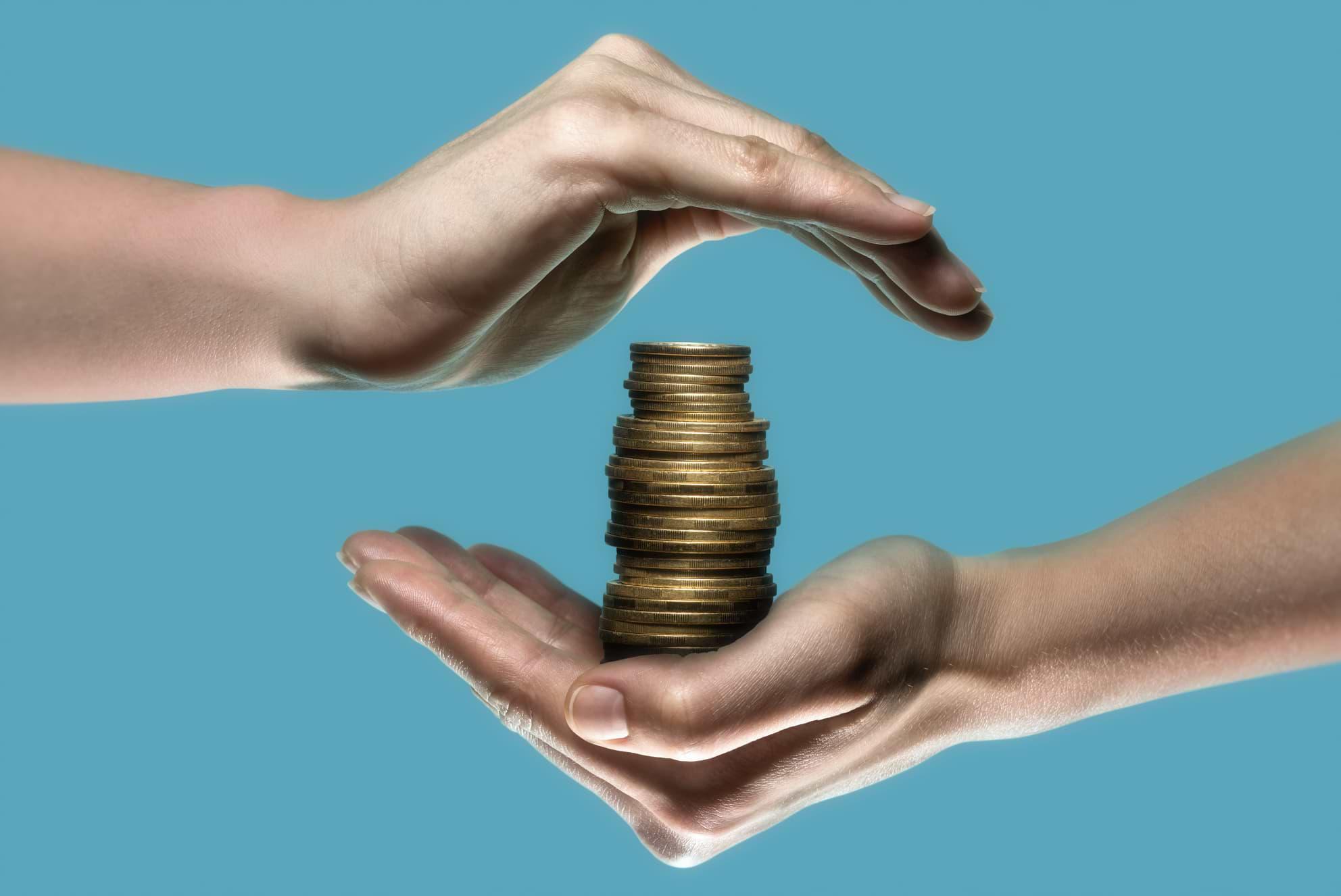 Händer som skyddar en hög med mynt