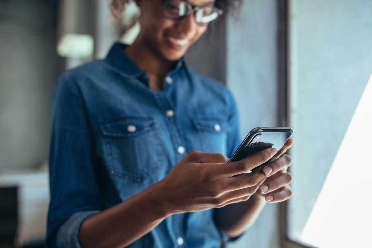 Kvinna som läser om lån på mobilen