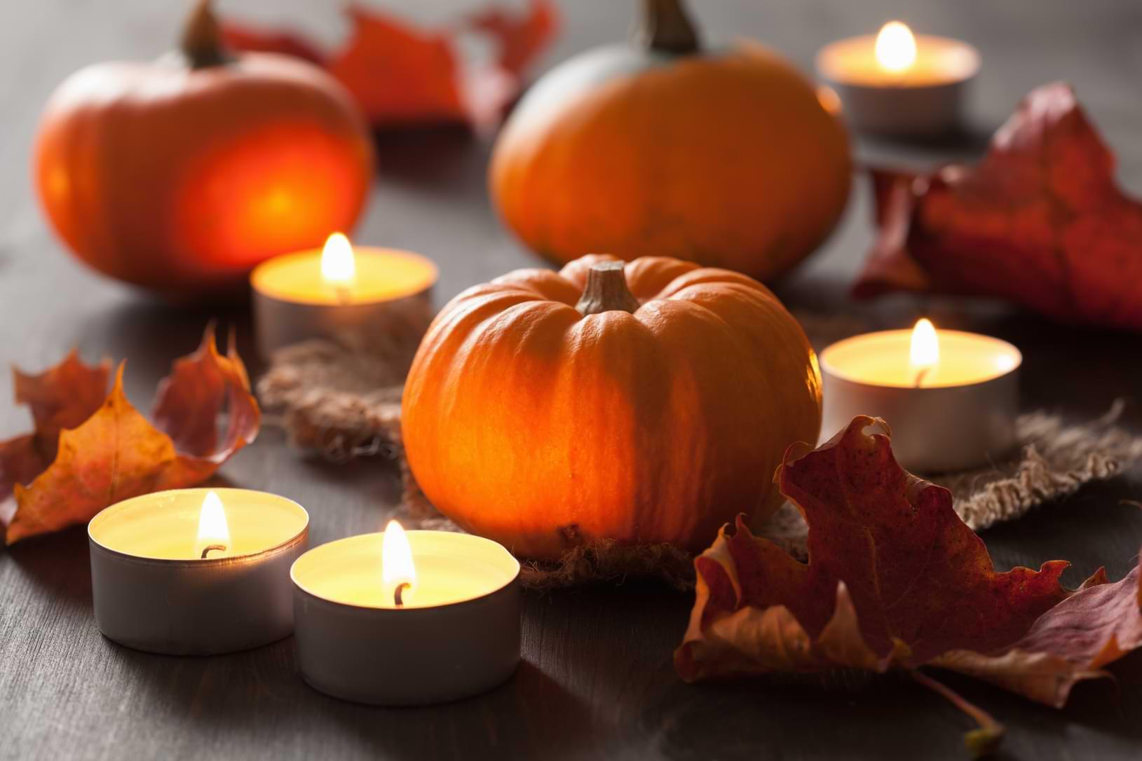 Pumpor, tända ljus och orange löv