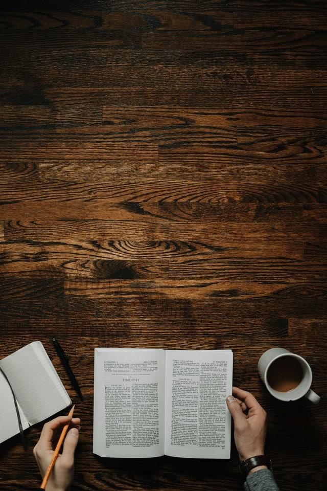 En man som sitter och läser en bok och dricker kaffe.
