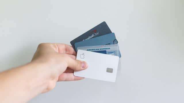 En hand som håller i en bunt kreditkort.