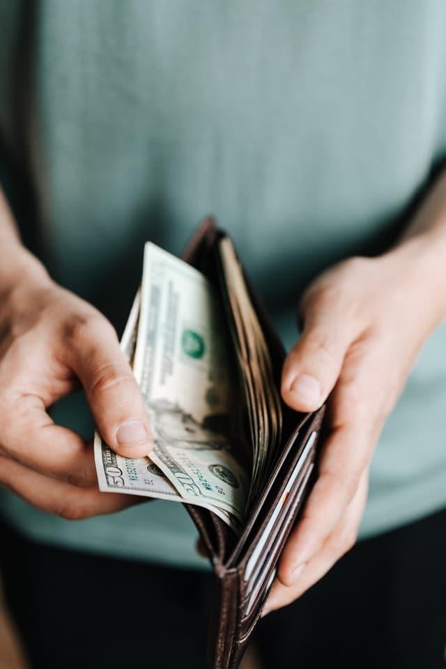 En man som håller i en plånbok med dollarsedlar.